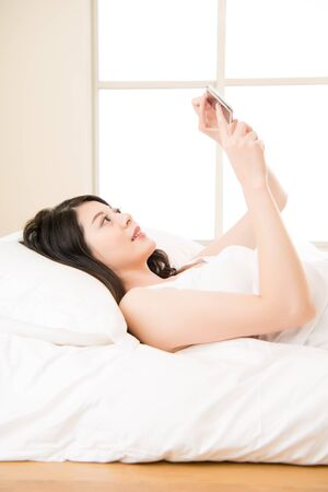 awake: Young smile asian woman reading smart phone on bed in bright room. home bedroom background Stock Photo