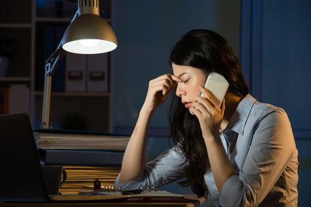 Asiatische Geschäftsfraukopfschmerzen auf dem Smartphone, das über Nacht spät arbeitet. Innen Büro Hintergrund Standard-Bild - 67907385