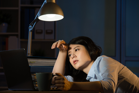 アジア ビジネス デスク眠い残業深夜で座っている女性。屋内オフィスの背景