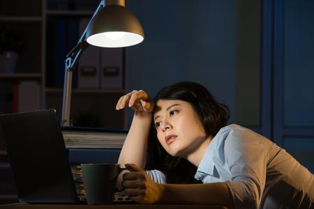 Aziatische zaken vrouw zitten aan de balie slaperig overuren 's avonds laat. binnenshuis kantoor achtergrond