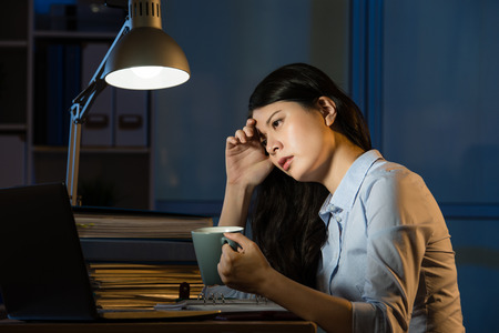 asian business woman drink coffee refreshing working overtime late night. indoors office background Stock fotó