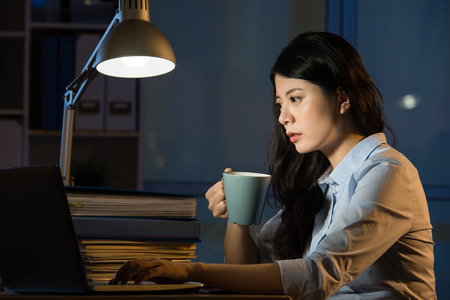 asian business woman drink coffee refreshing working overtime late night. indoors office background Stock Photo