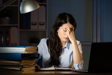 Femme d'affaires asiatique assis à son bureau des maux de tête des heures supplémentaires tard dans la nuit. intérieur fond de bureau Banque d'images - 67907420