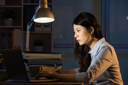 asian business woman sitting at desk working use laptop overtime late night. indoors office background 版權商用圖片 - 67907429