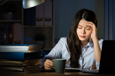 asian business woman drink coffee sitting at desk headache overtime working late night. indoors office background