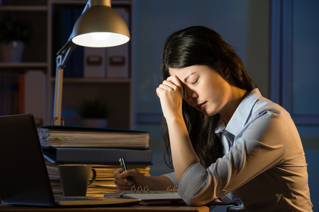 アジア ビジネスの女性デスク頭痛超過作業深夜で座っています。屋内オフィスの背景