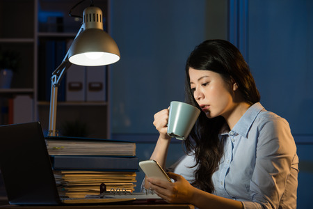 asian business woman talk on smartphone working overtime late night. indoors office background Stock fotó