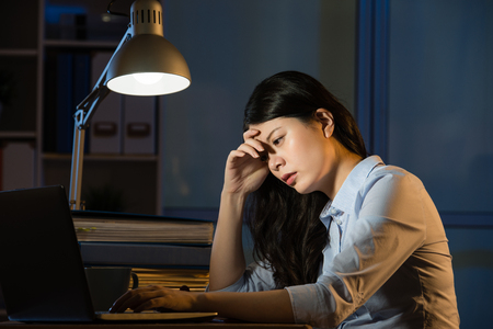 femme d'affaires asiatique assis au bureau endormi travaillant des heures supplémentaires tard dans la nuit. fond de bureau à l'intérieur