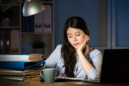 asian business woman sitting at desk working use laptop overtime late night. indoors office background Banque d'images