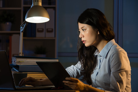 asian business woman touch screen on digital tablet working overtime late night. indoors office background 版權商用圖片 - 67907828