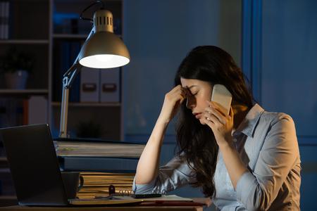 Asiatique femme d'affaires des maux de tête sur un smartphone des heures supplémentaires tard dans la nuit. intérieur fond de bureau Banque d'images - 67907836