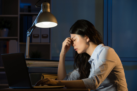 asian business woman sitting at desk headache overtime working late night. indoors office background 版權商用圖片 - 67907837