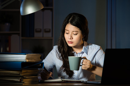 asian business woman drink coffee sitting at desk working use laptop overtime late night. indoors office background