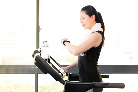 Beautiful asian woman running treadmill use smartwatch check pulse rate. indoors gym background. health sport concept