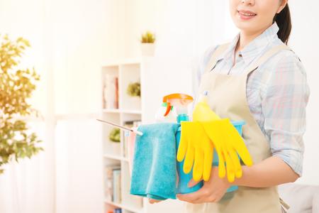 De glimlachende gelukkige klaargemaakte de holdingsemmer van de huisvrouwen klaar vult omhoog met detergens voor het schoonmaken van huis bij woonkamer. gemengd ras Aziatisch Chinees model.