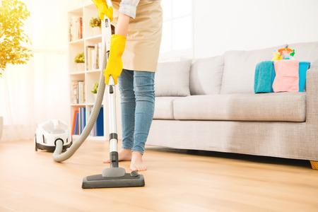 거실 바닥을 청소하는 여자 사용 진공 청소기. 집안일 개념. 혼혈 아시아 중국 모델.
