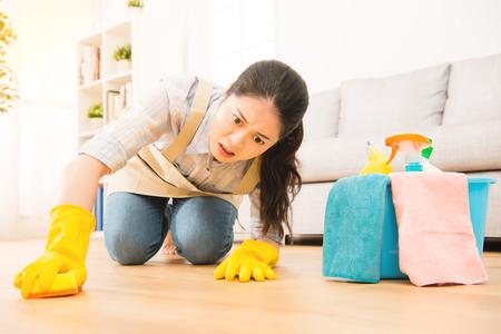 Ménagère gommage peine nettoyage plancher dans des gants de protection avec l'expression du visage de la lutte à genoux sur le sol en bois à la maison. race mixte modèle asiatique chinois. Banque d'images - 68147941