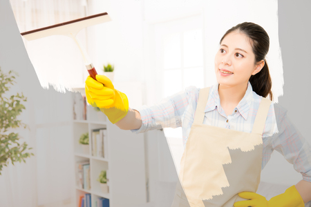 Happy woman in gloves cleaning window with rag at home. Large window glass in foam. Housework concept. mixed race asian chinese model. Stock Photo