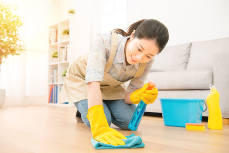 Sonriente mujer ama de casa en guantes amarillos lavar el piso con trapo y detergente. Modelo asiático chino de la raza mezclada Foto de archivo