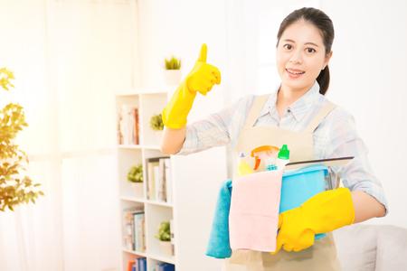 De mooie vrouw houdt een bassin met detergentia en vodden die duimen op gebaarteken tonen, camera bekijken en klaar glimlachen om haar huis schoon te maken. gemengd ras Aziatisch Chinees model.