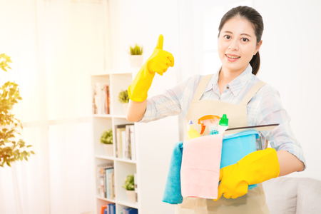 Beautiful woman is holding a basin with detergents and rags showing thumbs up gesture sign, looking at camera and smiling ready to clean her house. mixed race asian chinese model. Archivio Fotografico