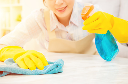 Young Cheerful housewife in yellow gloves cleaning table of living room and smiling at home. mixed race asian chinese model.