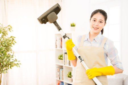 housewife cleaning wooden floor with vacuum cleaner in living room. Housework concept. mixed race asian chinese model. Standard-Bild