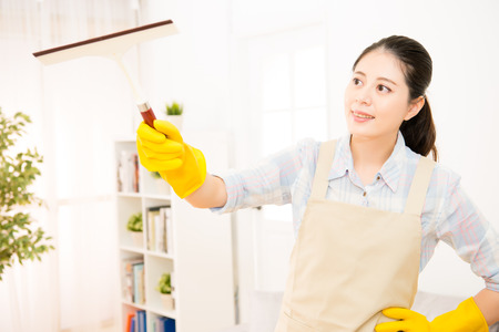 domestic chores: A portrait of a Beautiful young asian women doing domestic chores using glass cleaning wiper at living room. mixed race asian chinese model.