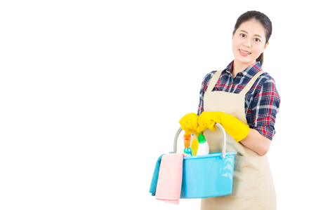 Young woman holding cleaning tools and products in bucket isolated on white background. Beautiful fresh energetic multiracial Chinese Asian female model.