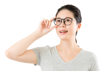 attempt: beautiful asian woman try on new glasses for choice. isolated on white background. medical and health concept Stock Photo