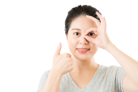 beautiful asian woman show ok gesture and thumbs up for good eye vision. isolated on white background. medical and health concept