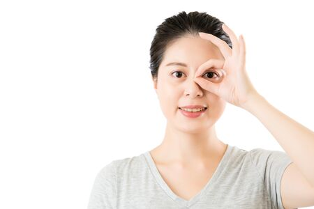 beautiful asian woman show ok gesture for good eye vision. isolated on white background. medical and health concept
