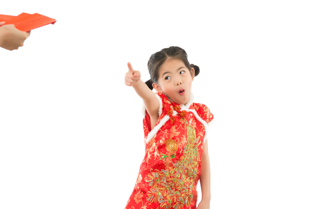 little asian chinese girl pointing ask for red lucky envelope money for buying her dreaming toy. isolated on white background. holiday and festival concept.