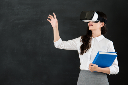 asian woman teacher touch screen with virtual reality. VR headset glasses device. blackboard background. school and education concept