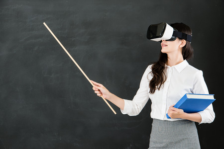 asian woman teacher teach with stick and virtual reality. VR headset glasses device. blackboard background. school and education concept