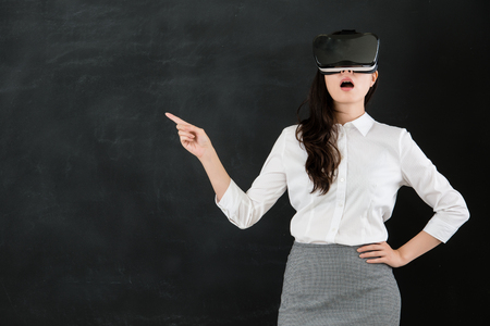 asian woman teacher pointing with virtual reality. VR headset glasses device. blackboard background. school and education concept
