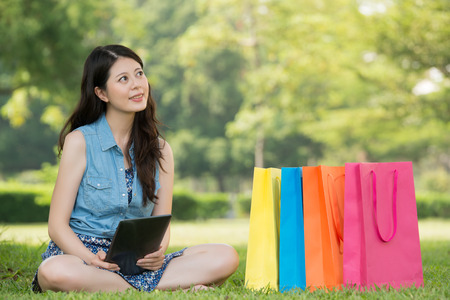 beautiful asian woman using digital tablet thinking shopping online sitting on grass. outdoors background. technology and people concept Stock Photo