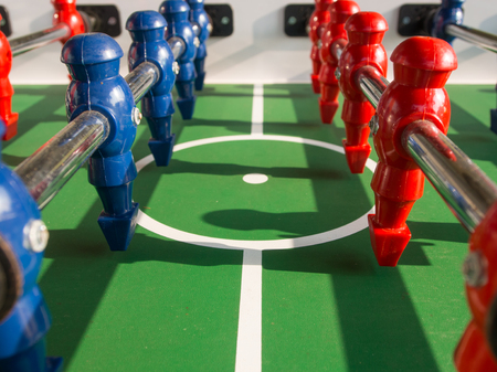 Table football game with red and blue players team in table soccer or football kicker game,