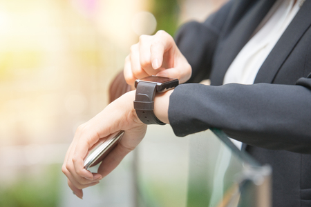 business technology time and people concept. close up of woman hands setting smart watch outside of office. mixed race asian chinese on blurred background. Stock Photo