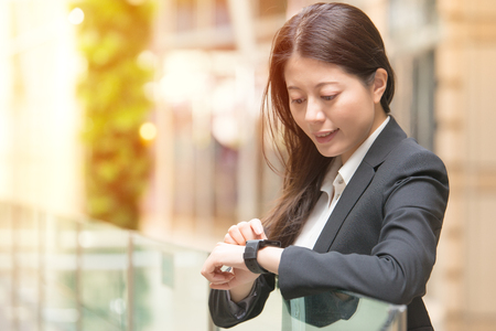 technology and people concept. Happy business woman looking at her smartwatch. mixed race asian chinese on blurred background. Stock Photo