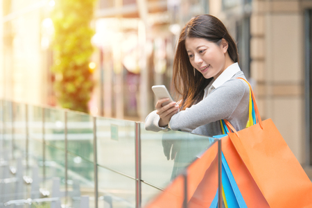 Happy girl holding bags with purchases smiling while looking at phone in shopping center. received good news and reading message texting using app on smartphone. Mixed race Asian female model Stock Photo