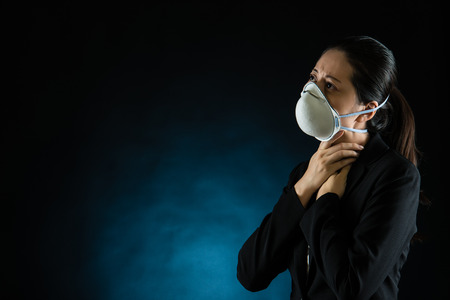 unhappy business woman feel sick wearing a face mask to deal with virus or pollution. mixed race asian chinese model Stock Photo