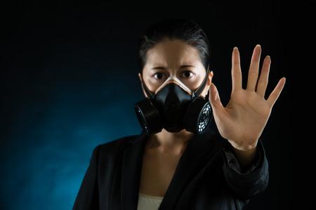 Mujer en máscara protectora con gesto de rechazo. La contaminación atmosférica influencia smog en el concepto de salud de las personas. modelo chino asiático de raza mixta Foto de archivo - 75842914