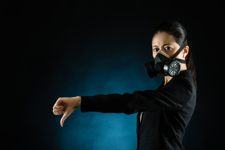 mixed race business woman showing thumbs down hand gesture wearing a face mask to dislike pollution. Young multiracial Asian chinese female model
