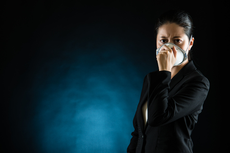 portrait of young business woman wearing a mask on black background concept of pollution. mixed race asian chinese model