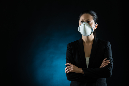 transmissible: Person wearing protective mask against transmissible infectious diseases and as protection against pollution and the flu. Beautiful mixed race asian chinese model Stock Photo