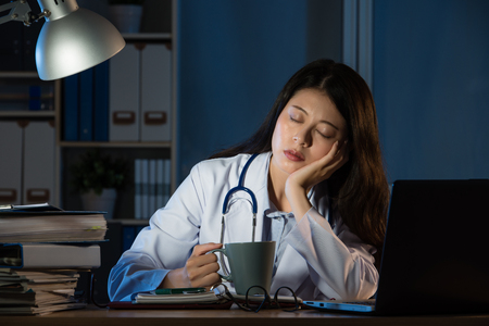 exhausted medical personnel sleeping with coffee after night shift at late night. pretty mixed race asian chinese woman model. medical and health concept