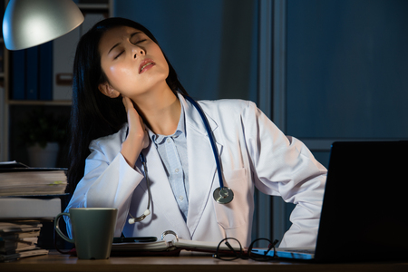 背中の痛みを強調して首をこらえて疲れの女性医師。美しい混血アジア中国の女性モデル 写真素材