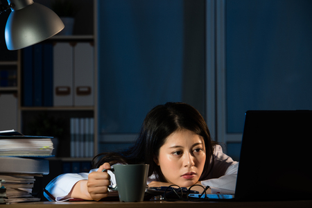 Image of sleepy doctor with coffee working at office tired after busy day night shift trying to stay awake. mixed race asian chinese woman model