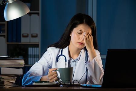Closeup ritratto triste infelice professionale di assistenza sanitaria con mal di testa ha sottolineato la tazza di caffè sonnolenta azienda. Medico dell'infermiera con emicrania sovraccaricato sovraccaricato. abbastanza razza mista asiatica cinese donna modello